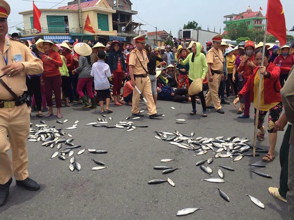 越南廣平省廣澤縣的遊行活動,民眾丟出不能販賣的死魚抗議。圖片來源:越南最前線。