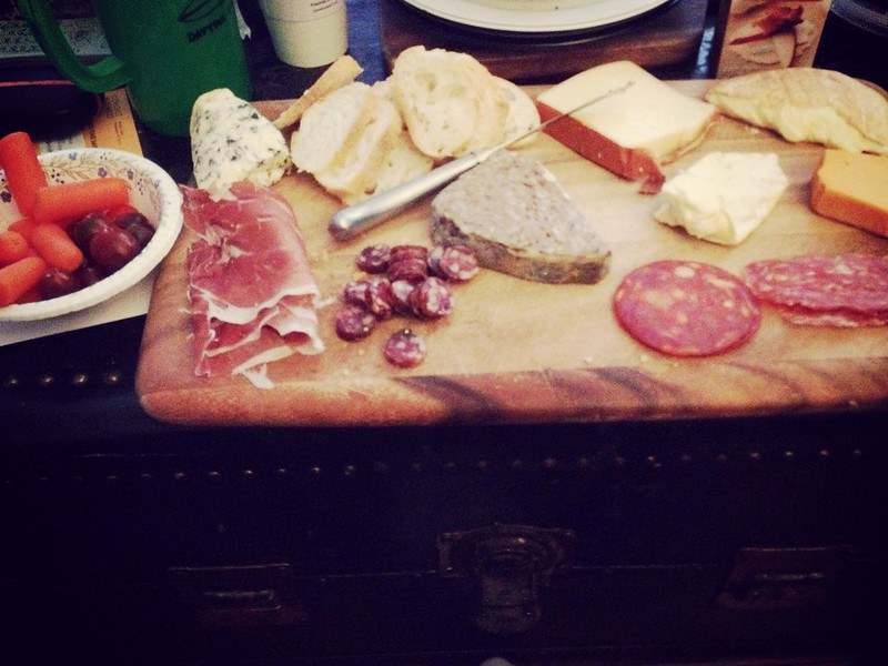 Leftover cheeses, cured meats, and even a few veggies on a cutting board in my living room.