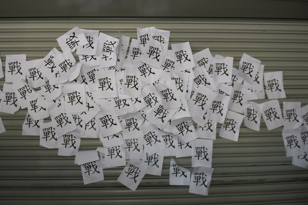 群眾將印有「戰」字的紙張貼華航分公司的一樓鐵門。(攝影:宋小海)