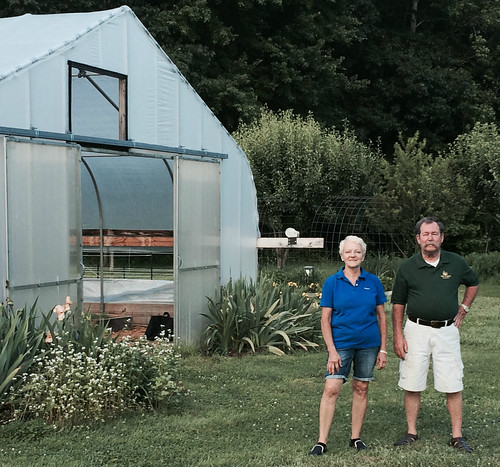 Farmers Scott and Susan Hill in front of their pollinator garden