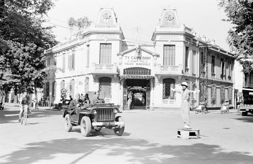 HANOI 1950 - Street scene with jeep in front of Hanoi poli ...