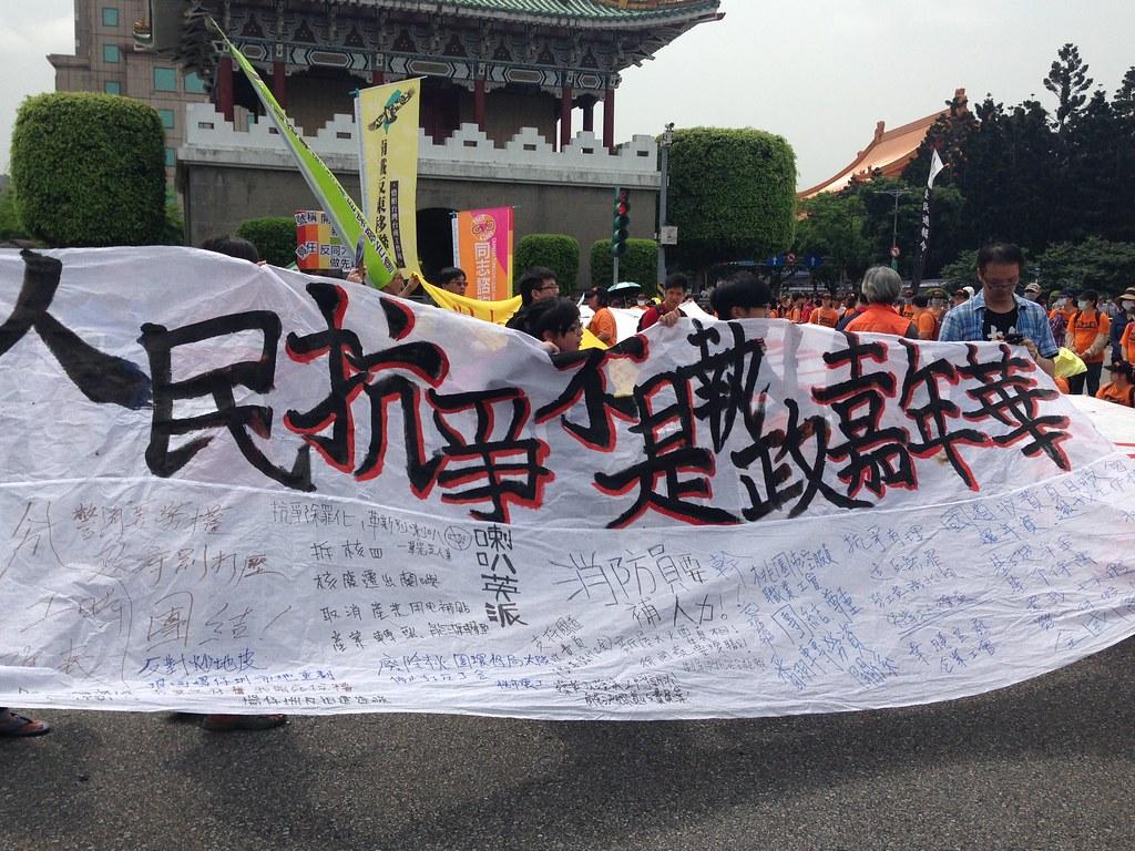 日前民進黨於就職典禮搬出社運抗爭的戲碼與標語的爭議,真抗議的民間團體拉著「人民抗爭不是執政嘉年華」的旗幟。(攝影:張宗坤)