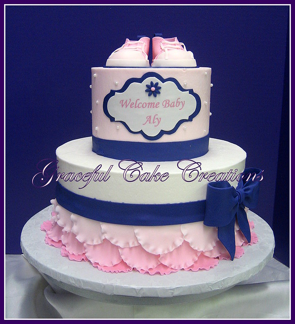elegant pink and purple baby shower cake with pink tennis shoes