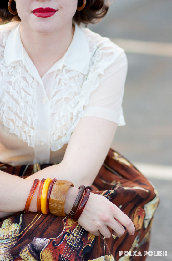 Bakelite bangles bring out the warm colors in a novelty print 1950s skirt featuring violins and sheet music.