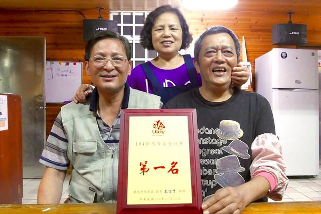 合作社主席周志國(左)與葛思悠農場主人夫婦合影。攝影:許宏偉。