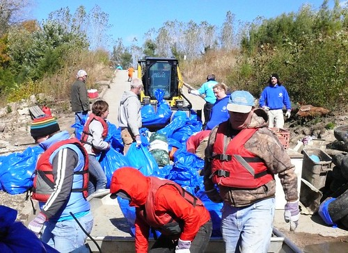 Volunteers unloading tires and bags of trash into the front loader for final disposal.