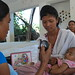 Using a timer, an FCHV in Nepalgunj counts a child's respiratory rate to confirm a diagnosis of a possible respiratory infection.