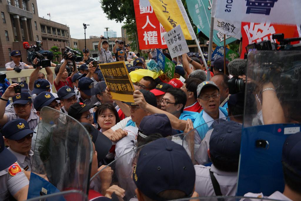 勞團與警方在行政院前短暫推擠,隨後轉往立法院。(攝影:王顥中)