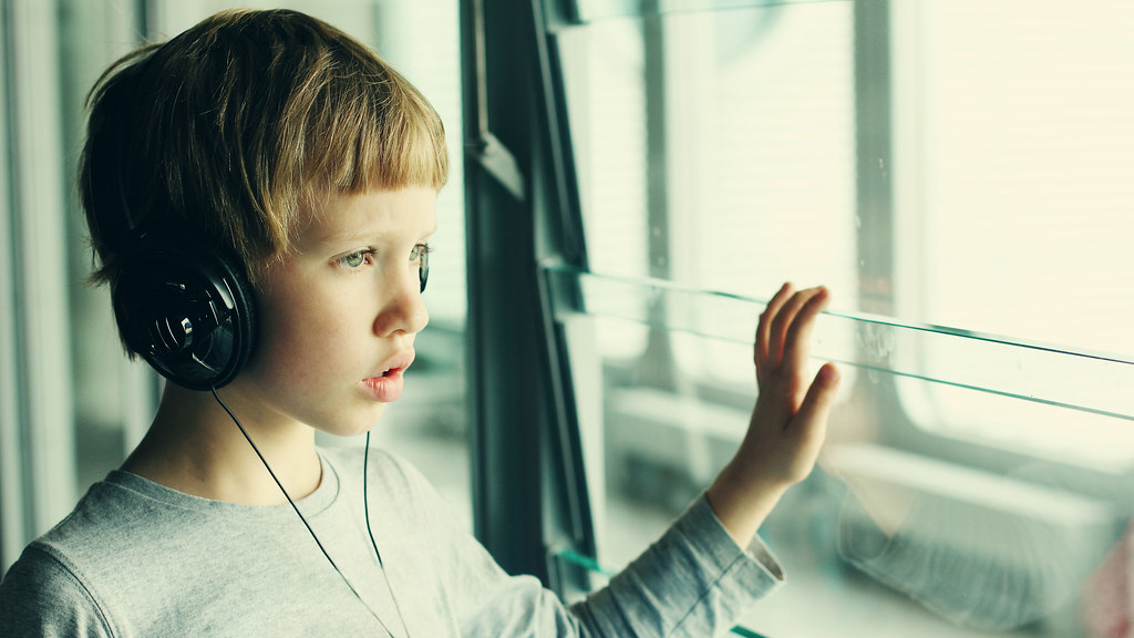 A boy wearing headphones looking out of a window. Photo from Shutterstock (260857394)