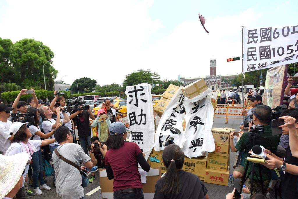 群眾紛紛拾起腳上鞋子,擊倒設置於總統府前的象徵金權紙箱高塔,誓言終止迫遷政策。(攝影:宋小海)