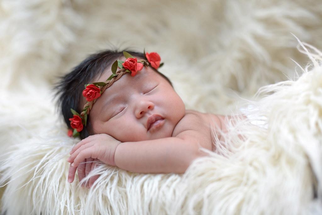 cute asian baby girl sleeping on furry cloth wearing roses