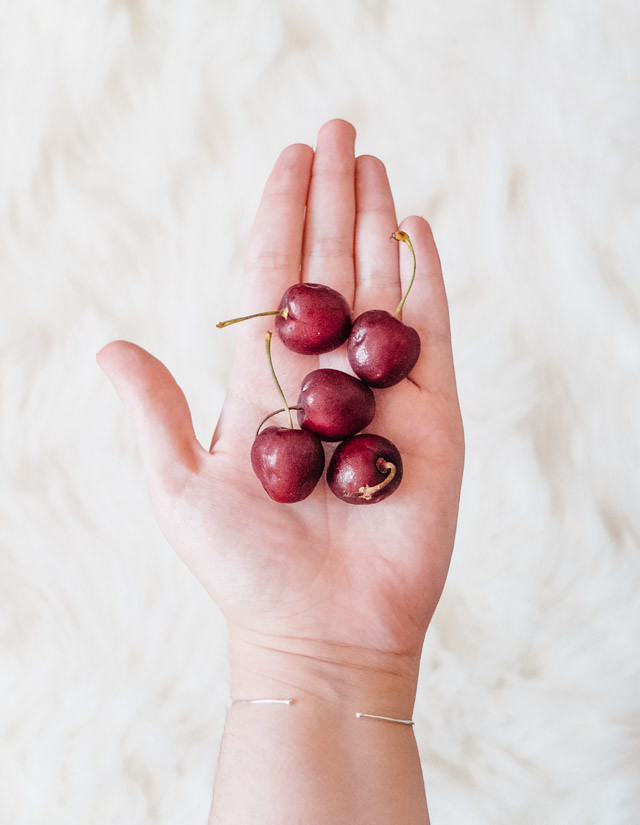 hand holding cherries
