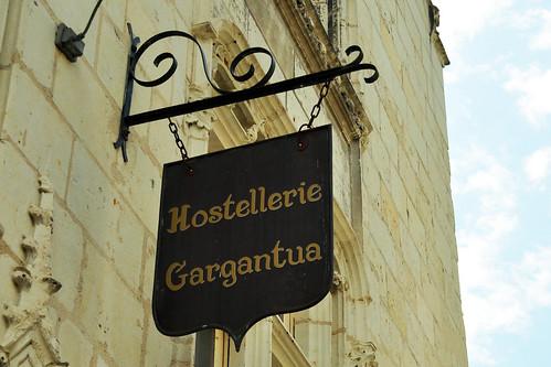 """Hier sitzt er, der berühmteste Sohn der Stadt Chinon: François Rabelais, geboren 1499 allhier, gestorben 1552 in Paris. In Chinon taucht sein Name vielerorten auf: Restaurants sind nach ihm benannt, Straßen, Plätze. Rabelais war Arzt, Heiler, Bettelmönch, Satiriker … einer der bedeutendsten französischen Renaissance-Schriftsteller und noch dazu einer, an dem sich die Geister scheiden. Sein Romanzyklus """"Gargantua und Pantagruel – ein Werk übermütiger Sinnesfreude"""" ist Literatur-Interessierten ein Begriff. Ganz besonders natürlich in seinem Heimatland Frankreich, wo sich bis heute viele Redewendungen der Alltagssprache auf Rabelais und seine Bände beziehen und sich mittlerweile verselbstständigt haben: un appétit pantagruélique – ein pantagruelischer Appetit / un repas gargantuesque - ein gargantuesker Schmaus usw. Auch seine Zitate, Aussprüche, Aphorismen sind nach wie vor bekannt: """"Der Appetit kommt beim Essen. – Besser ist's, zum Lachen schreiben denn zum Weinen; eigenstes der Menschen ist das Lachen. – Eine gesunde Seele kann nicht in einem trockenen Körper wohnen. – Zieh den Vorhang, die Komödie ist aus."""" Ironie, Witz, Sarkasmus und derber Realismus prägen sein Werk. Bedenkt man zum Beispiel die in """"Gargantua und Pantagruel"""" in obszöner Sprache und peinlichster Ausführlichkeit dargelegte Abhandlung zum Thema, wie und womit man sich nach dem Toilettenbesuch den Popo abwischen sollte und dass dafür weiche, flaumige Entenküken am besten geeignet seien (ja pfui, die armen Tierchen!), kann man das Werk kaum als realistisch und derb, sondern muss es als sehr-sehr-sehr derb bezeichnen. Ähnliches gilt für Szenen zu Geschlechtsverkehr und üppigem Fressen. Ein extrem """"sinnenfreudiges"""" Werk für starke Nerven. Test und Foto: Brigitte Stolle, 2016"""