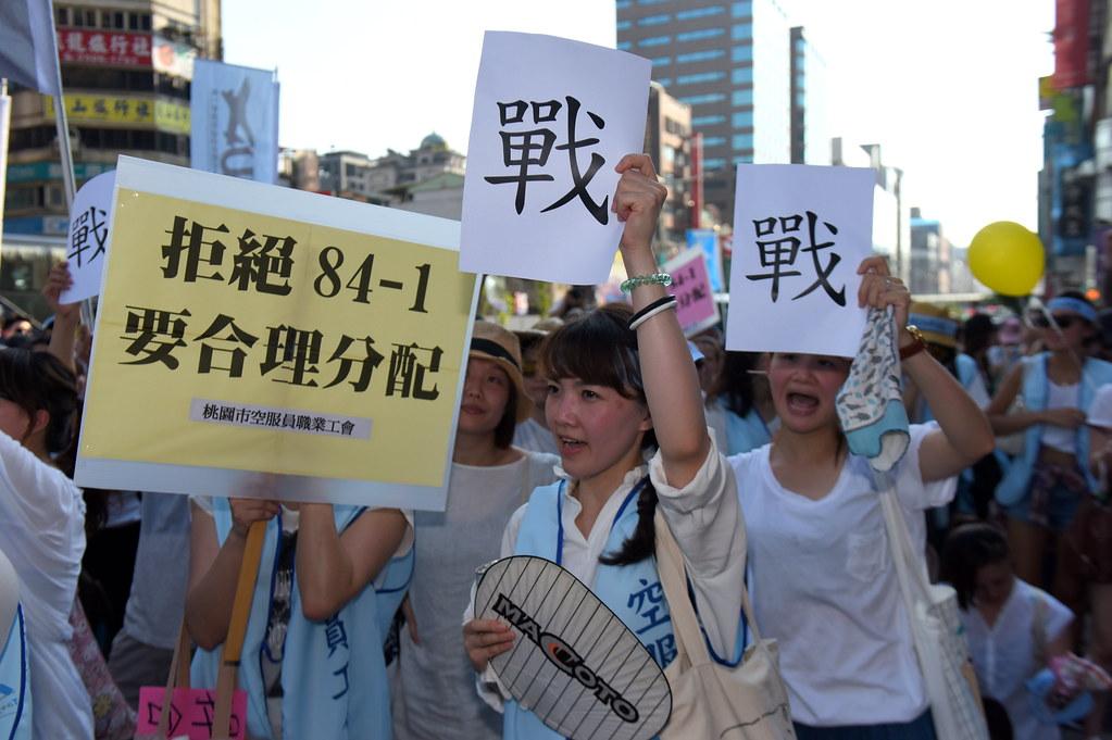華航勞工手持印有「戰」字的紙張,預告若華航不立即解決爭議,工會便會發起罷工行動。(攝影:宋小海)