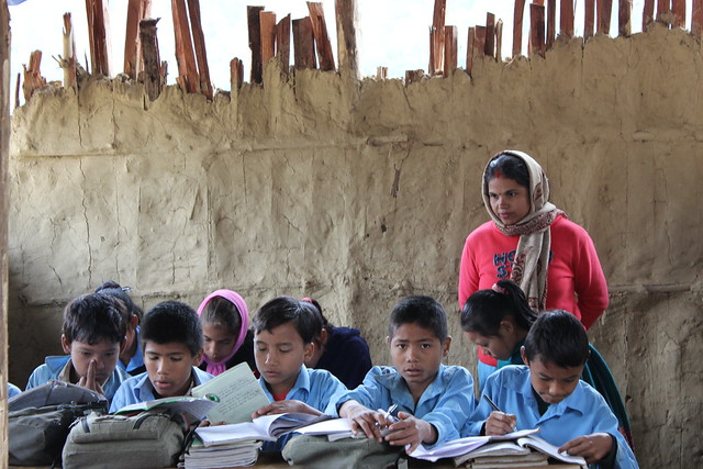 Kids work side-by-side at a temporary school for those displaced by floods in eastern Nepal. Many children experience trauma, fear or other psychological impacts of natural disasters, but few receive the necessary treatment. Credit: Mallika Aryal/IPS