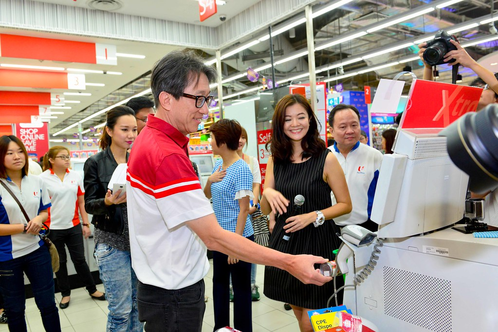 The self-service queue always moves faster than the traditional check-out counters! Minister for Manpower Lim Swee Say checks out the self-service system at a FairPrice outlet.