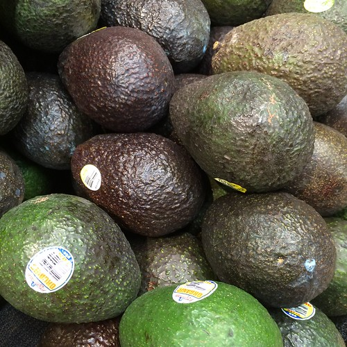 A pile of avocados of varying ripeness.
