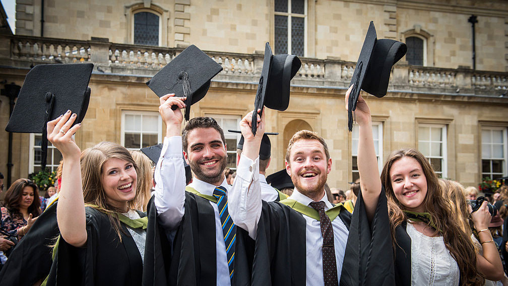 Four students holding their mortarboards