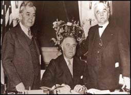 President Franklin Delano Roosevelt (center) signing the Rural Electrification Act