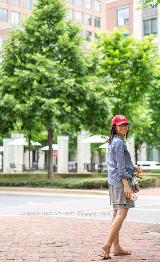 red baseball cap, chambray shirt, colorblocked crossbody bag, gray tiered dress, nude flip flops