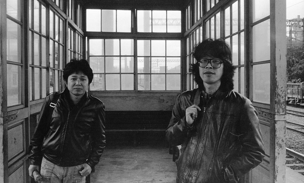 在桃園埔心車站候車的范振國(右)、盧思岳(左) 。1987年兩人辭去教職後,經常南北奔波,積極投入勞工和環保運動。 (攝影:蔡明德)