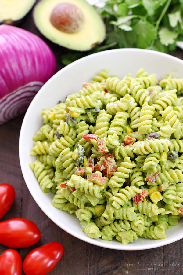 Avocado-Cilantro Pasta Salad in a white bowl with fresh vegetables.