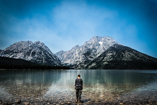 a picture of a woman standing in front of the Grand Tetons
