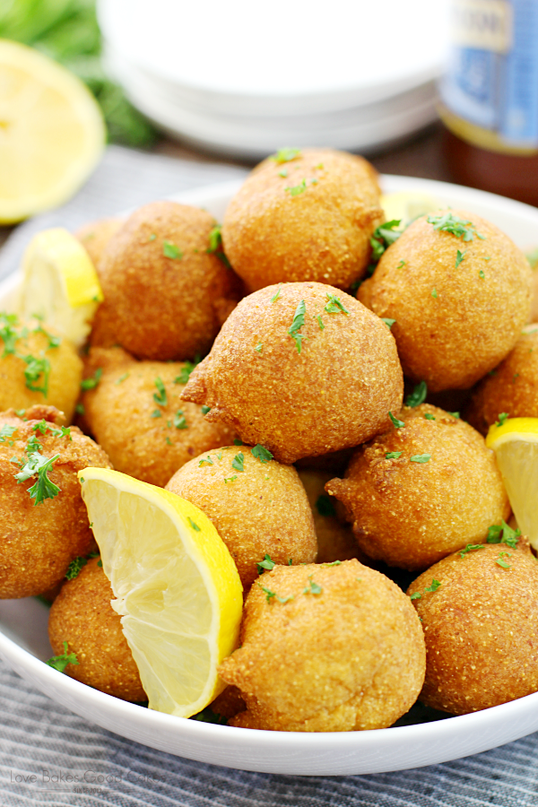 Classic Hush-puppies in a white bowl with slices of lemon.
