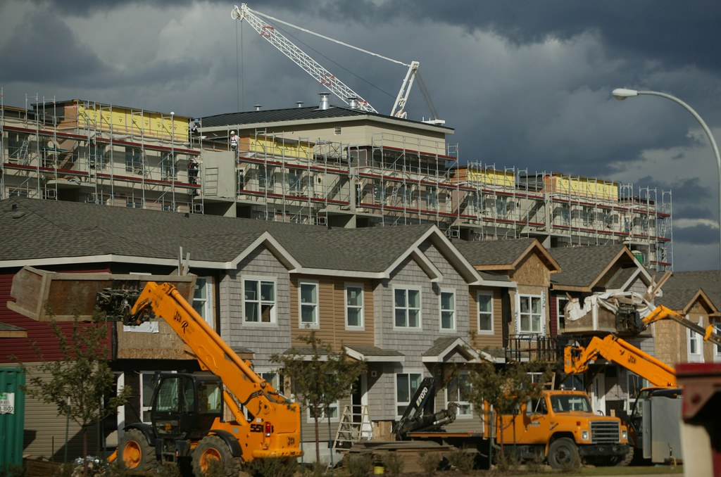 Photo of housing and an apartment building under construction