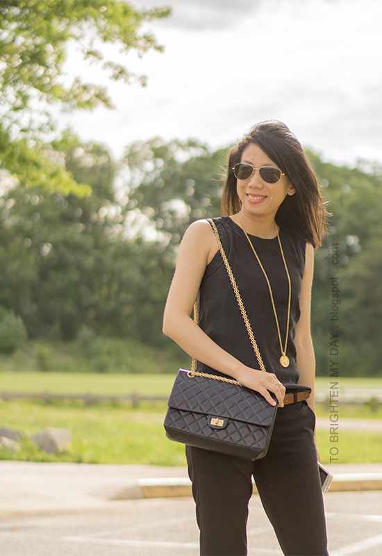 black sleeveless silk top, brown belt, gold jewelry, black pants