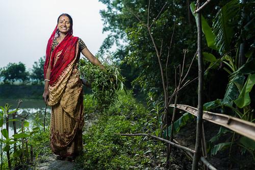Women farmer in Bangladesh holding her harvest