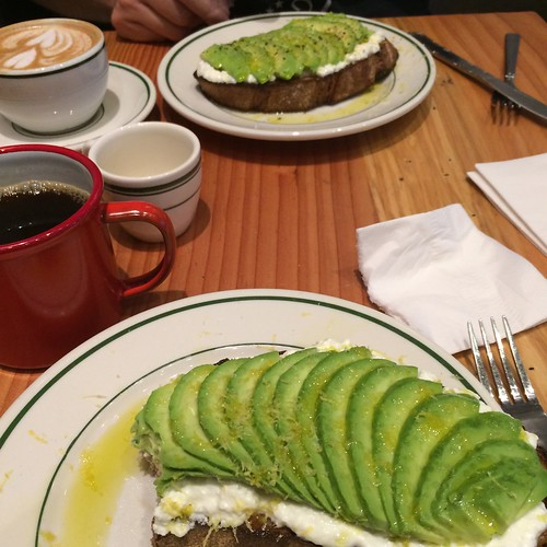 A table with avocado toast nearest the camera and another avocado toast in the background. A cup of coffee is near the nearer toast and a cappuccino is near the further toast.
