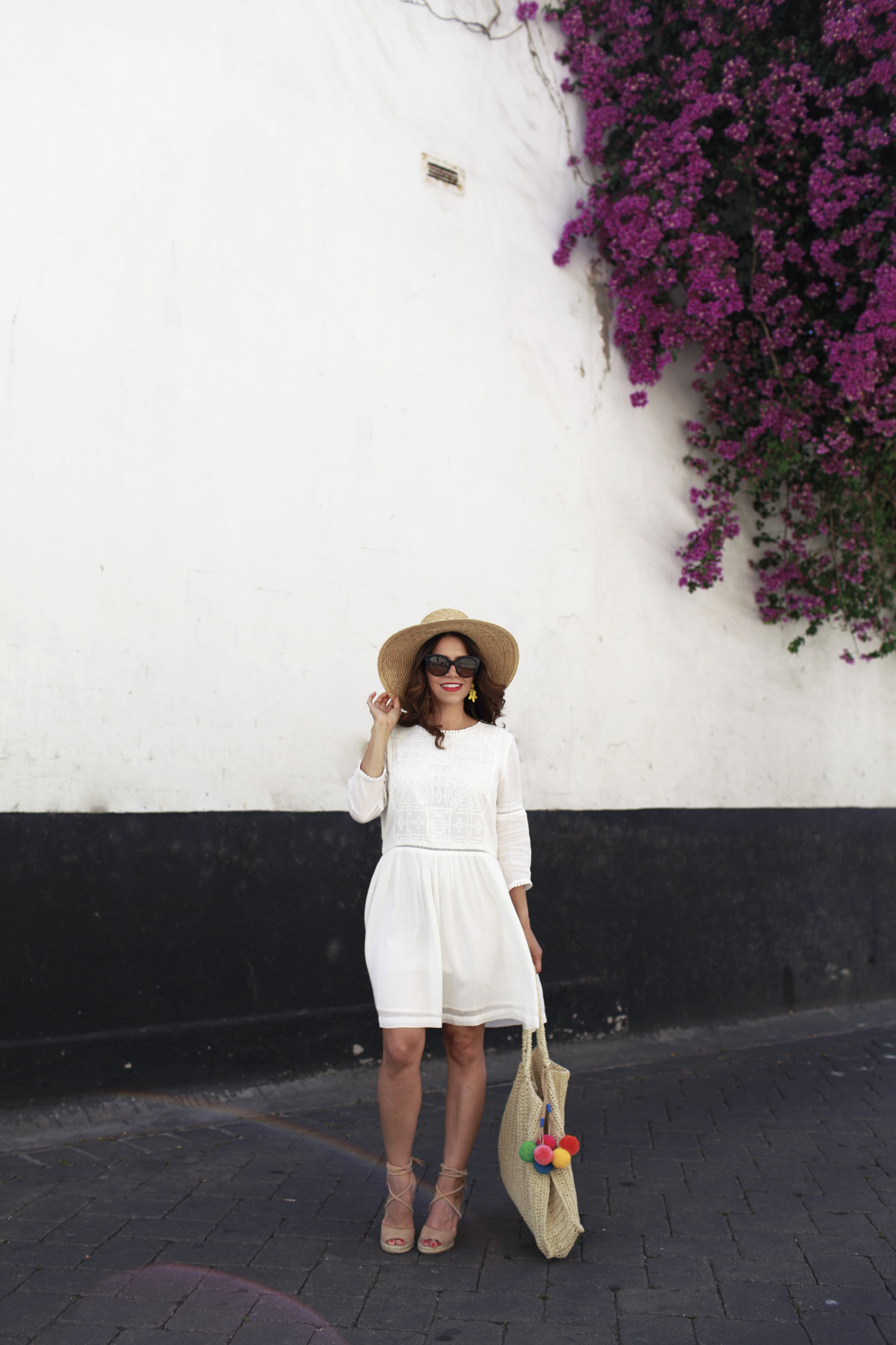 White summer dress with nude wedges and pom pom woven tote