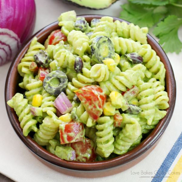 Avocado-Cilantro Pasta Salad in a brown bowl with an avocado and a red onion close up.