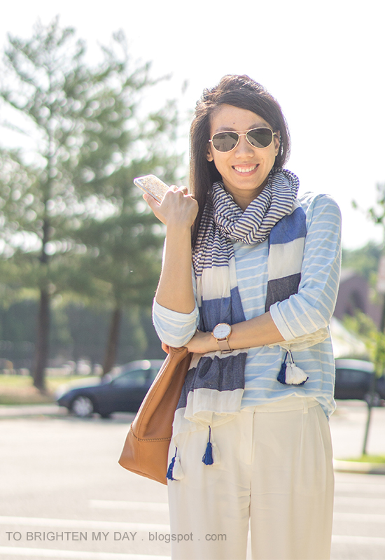 blue striped scarf with pom poms, blue striped top, white wide-legged trousers, oversized watch