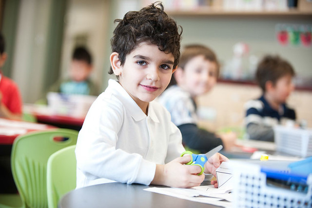 Photo of young boy sitting at a desk cutting paper with scissors
