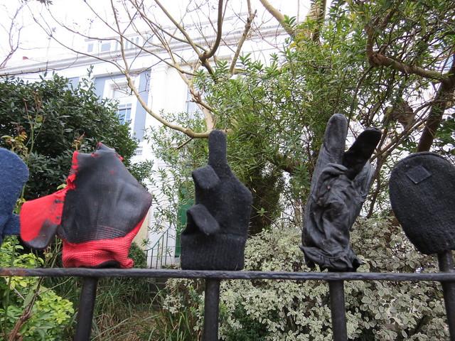 Random gloves on a fence
