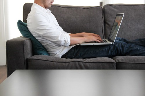 man-couch-typing-laptop