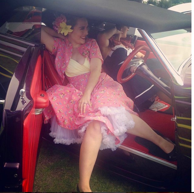 A woman poses in a retro car. She wears a 50s inspired shelf bust dress, kimono jacket and petticoats.