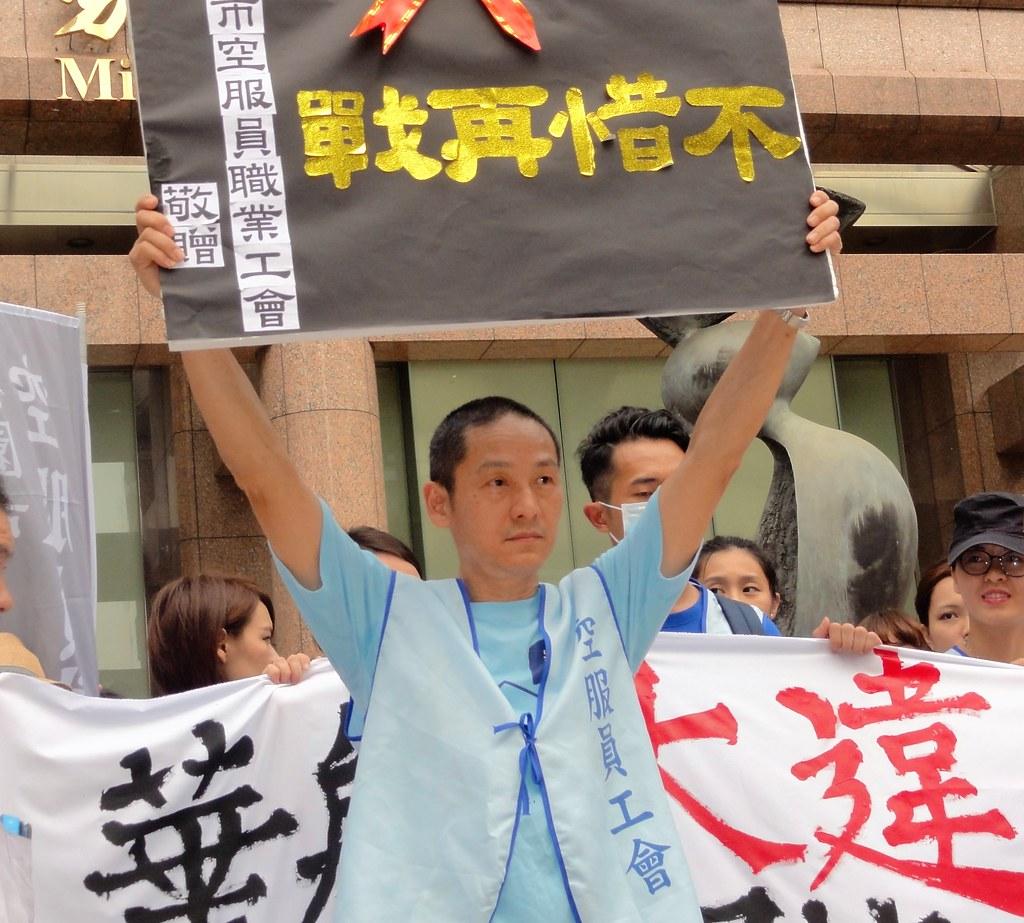 空服員工會理事長趙剛高舉上書「不惜再戰」四字的牌匾,先前這個牌匾曾作勢要送給桃園市勞動局。(攝影:張智琦)
