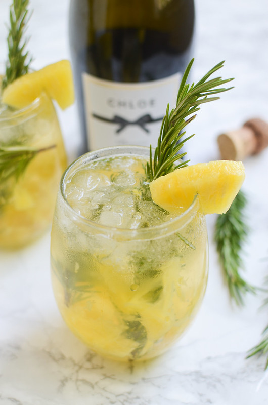 Pineapple Rosemary Crush - easy cocktail recipe with pineapple, rosemary, and sparkling wine! It looks fancy but it's inexpensive and serves a crowd!