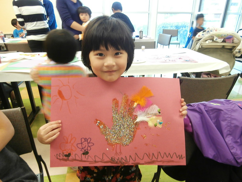 Child holding glittery turkey craft from Thanksgiving 2014 event.