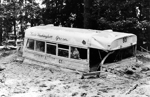 Image shows a school-type bus buried up to its hood in mud, with a screen of trees behind it. The top is dusted with ash. Some of the windows are shattered, and it's dented and sandblasted. The letters WEYERHAUSER COMPANY are just visible under mud spatters beneath the windows, and above the windows is cursive writing are the words