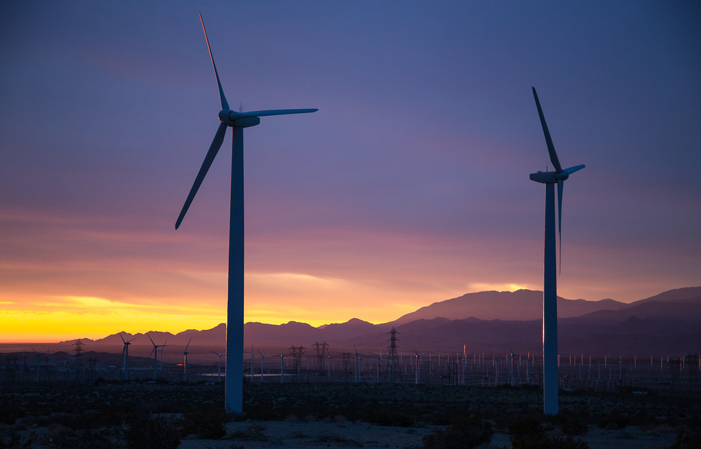 Two wind turbines in the foreground of a sunset