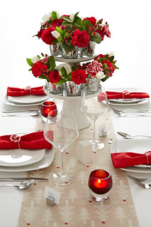 Table settings with red napkins, red glass candles, glasses, and a floral centerpiece with small miniature vases of carnations tulips and holly