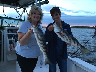 Photo of two women with their catch of striped bass