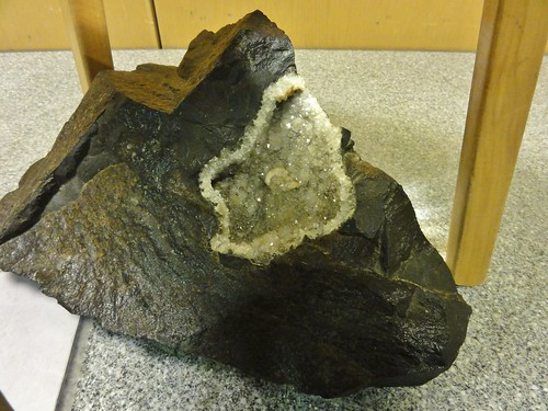 Image shows a pyramid-shaped piece of basalt with a large, crystal-filled cavity on the top and side.