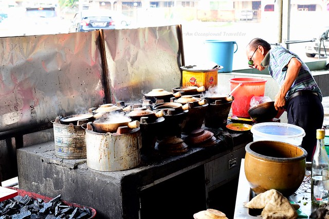 The cool man cooking claypot chicken rice over hot charcoal fire