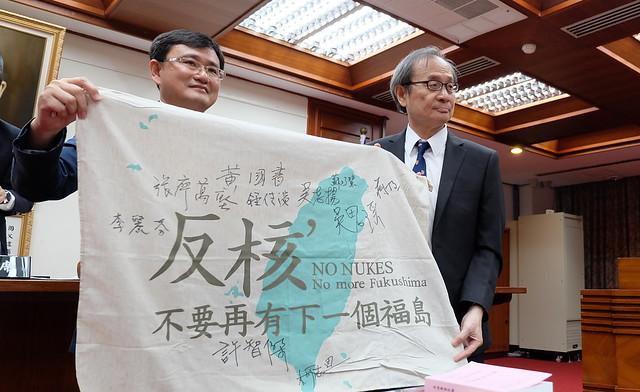 教育及文化委員會召委黃國書(左)將藍綠兩黨簽名的反核期送給新原能會主委謝曉星 攝影:陳文姿
