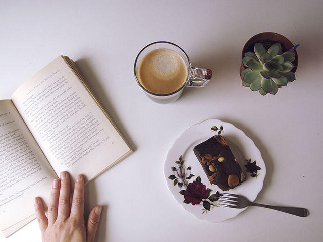 Vintage book reading with fresh nespresso coffee and peanut butter brownie